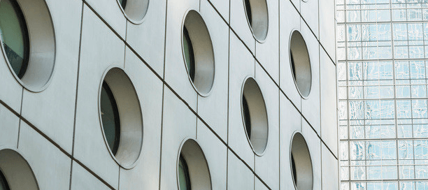 The side of a large building with circular windows.