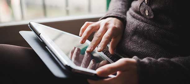A person's hand using an iPad near a window.