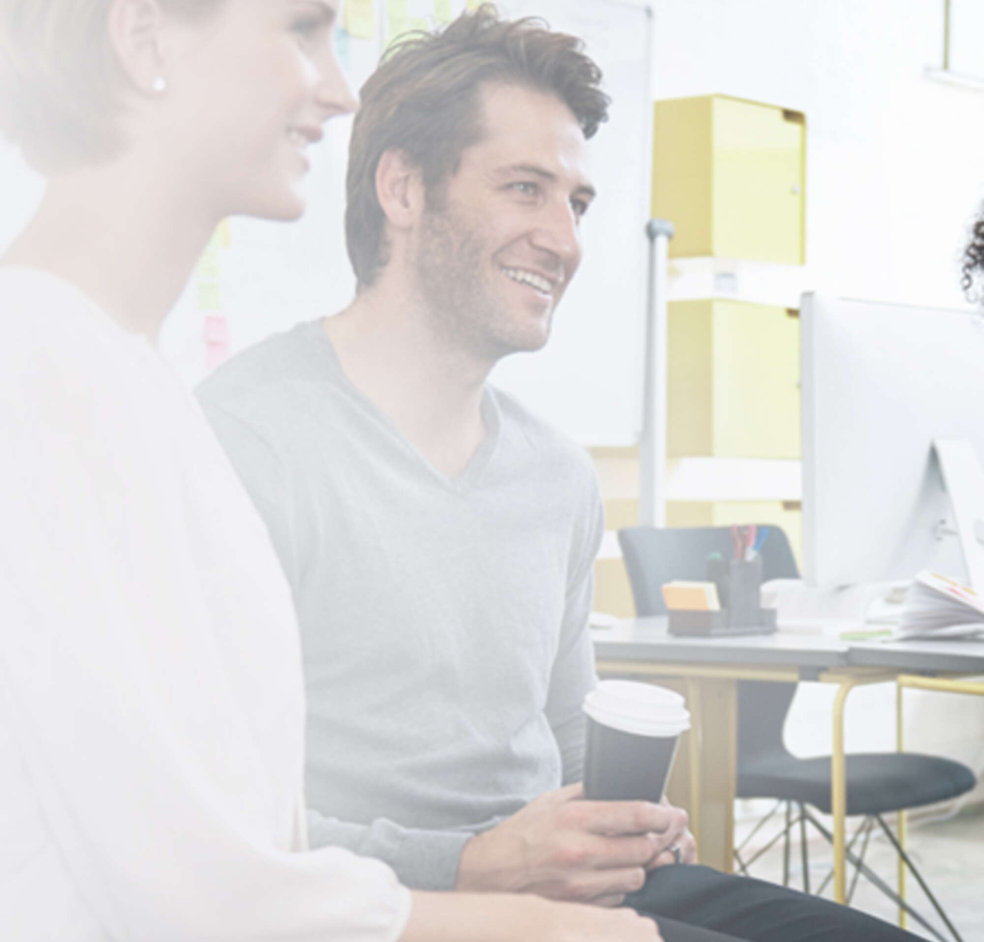 Two women and one man holding a coffee cup meet with a man in an office setting to discuss partner integrations.