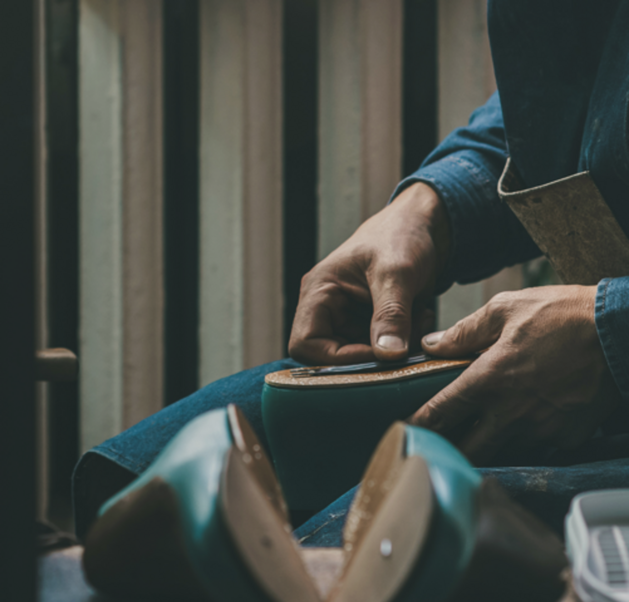 A shoemaker sitting in a workshop assembling the sole of a shoe.