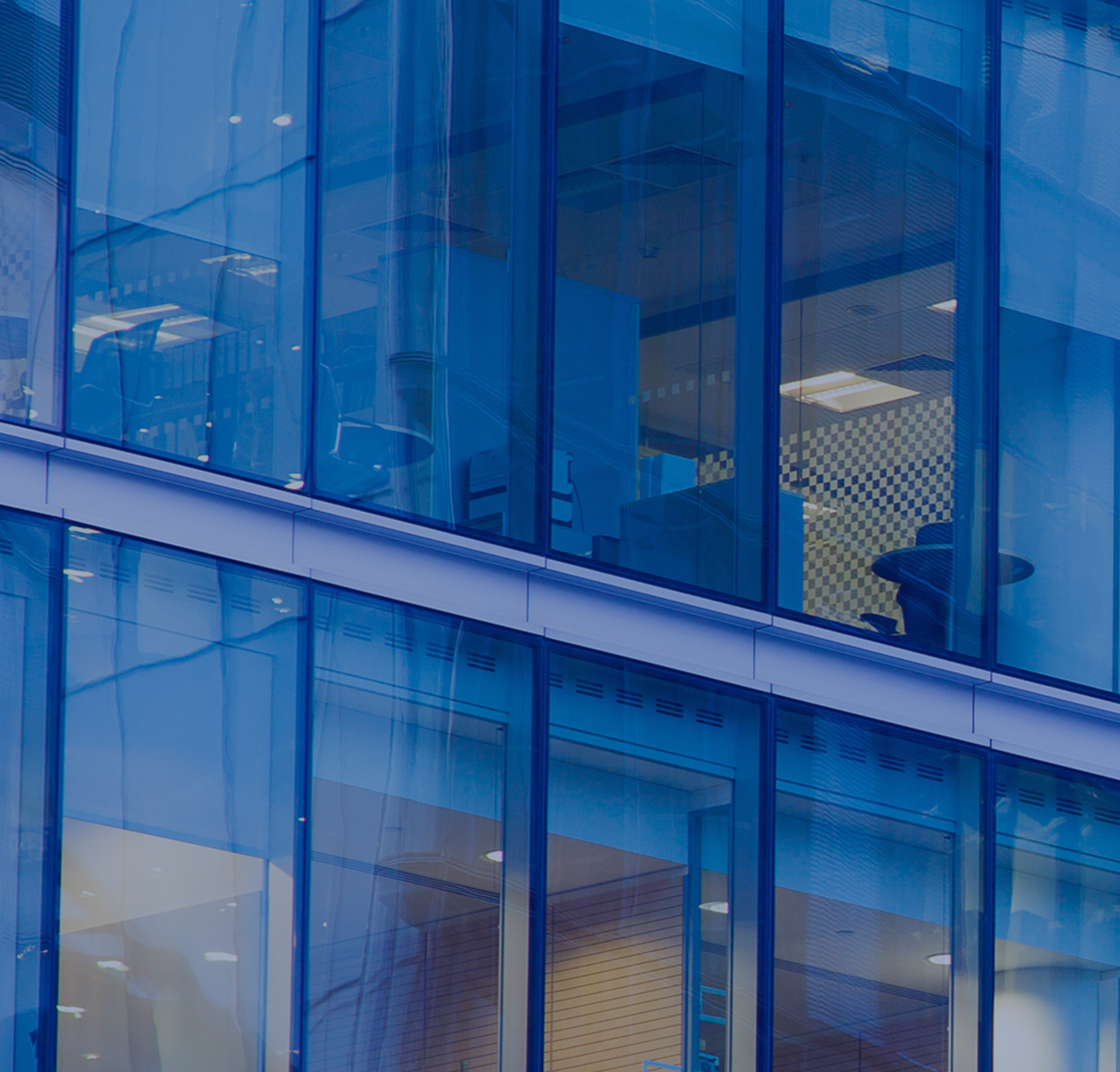 A tall glass office building with views into employees' work stations.