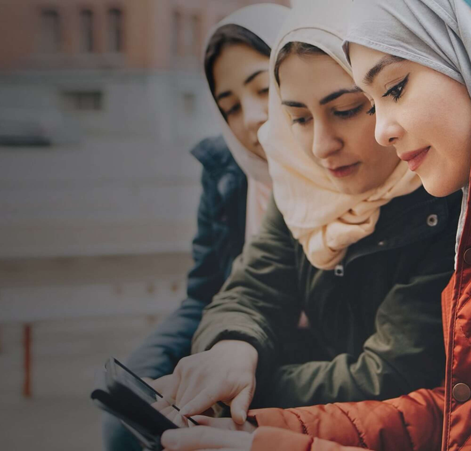 Four young women on a bench outside looking at a mobile device together.