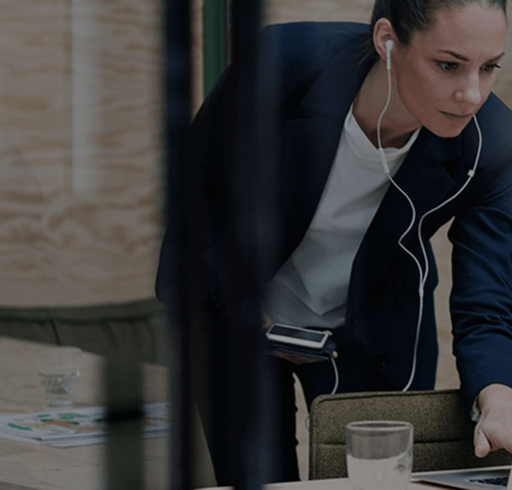 Woman with earbuds working on a laptop and holding her phone.