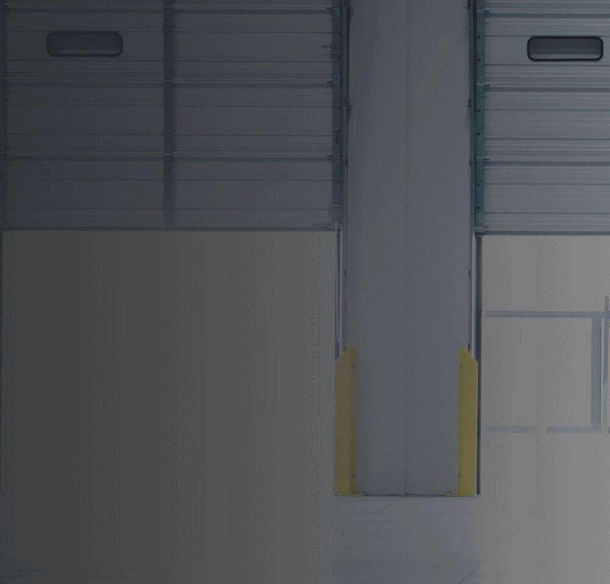 Man closing garage doors inside a warehouse.