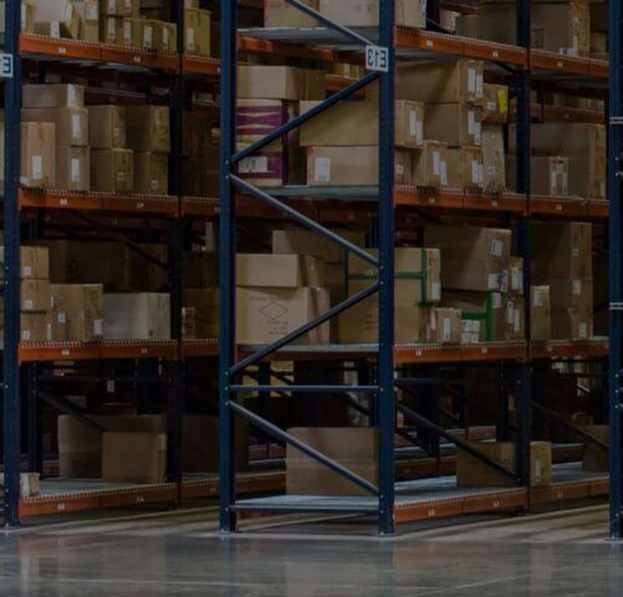 Two people in a warehouse full of boxes looking at an ipad while pushing a dolly.
