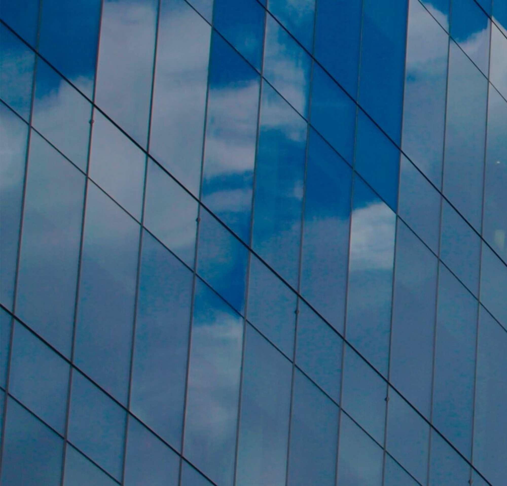 Fenêtres en verre d'un gratte-ciel dans lesquelles se reflètent les nuages.