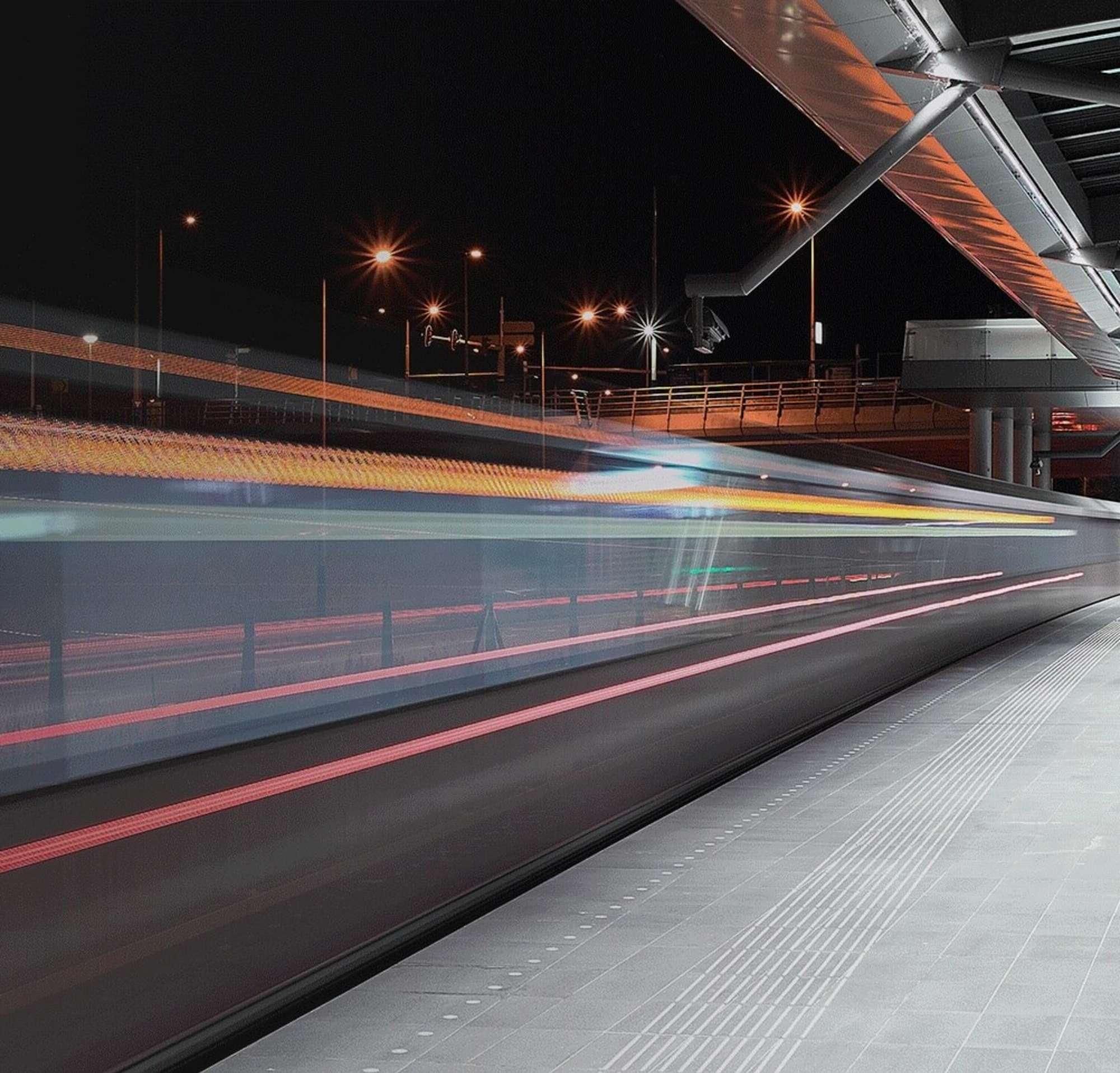A long exposure photograph of lightrail platform at night.