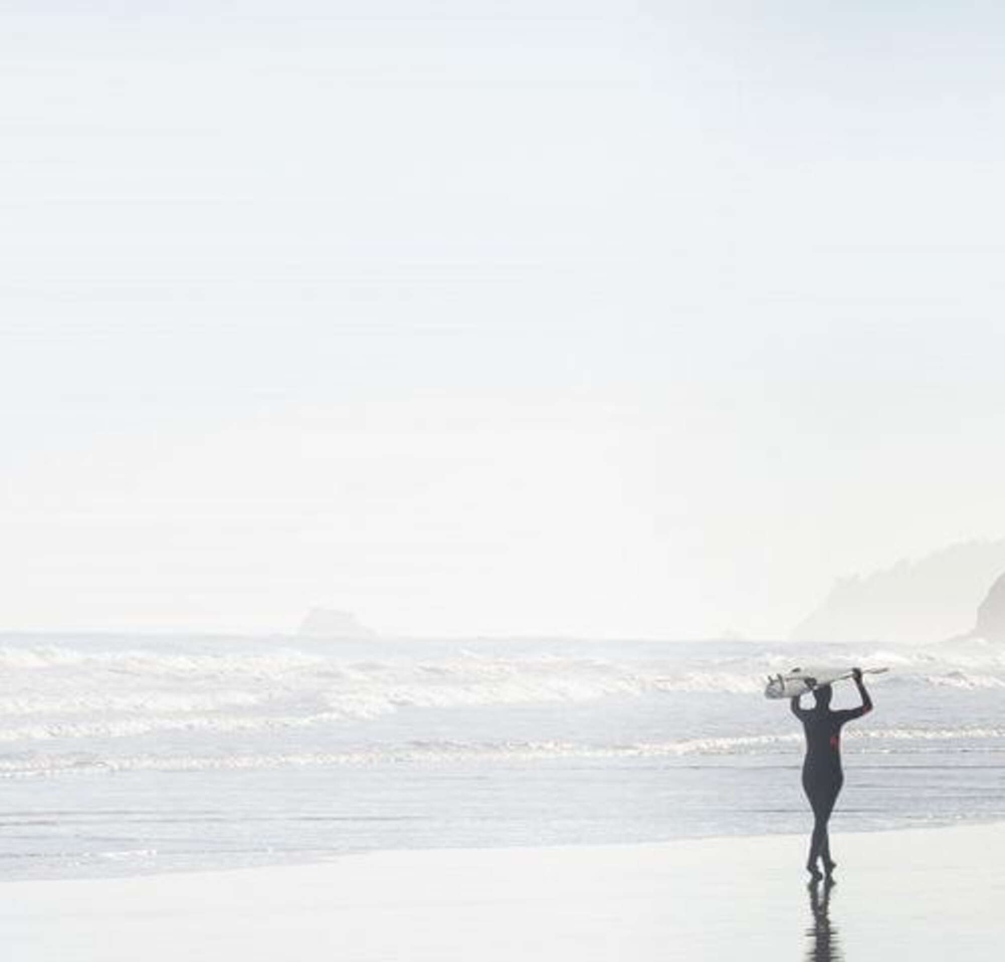 Two surfers walking together on a misty morning along a beach, carrying their surfboards above their heads.