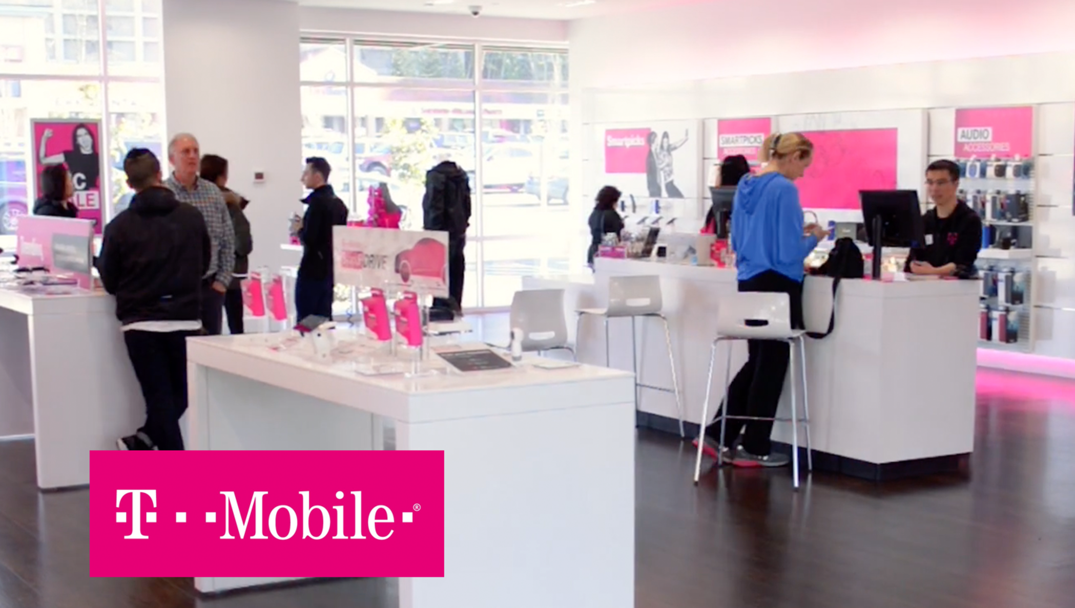 The interior of a T-mobile store with employees helping customers.