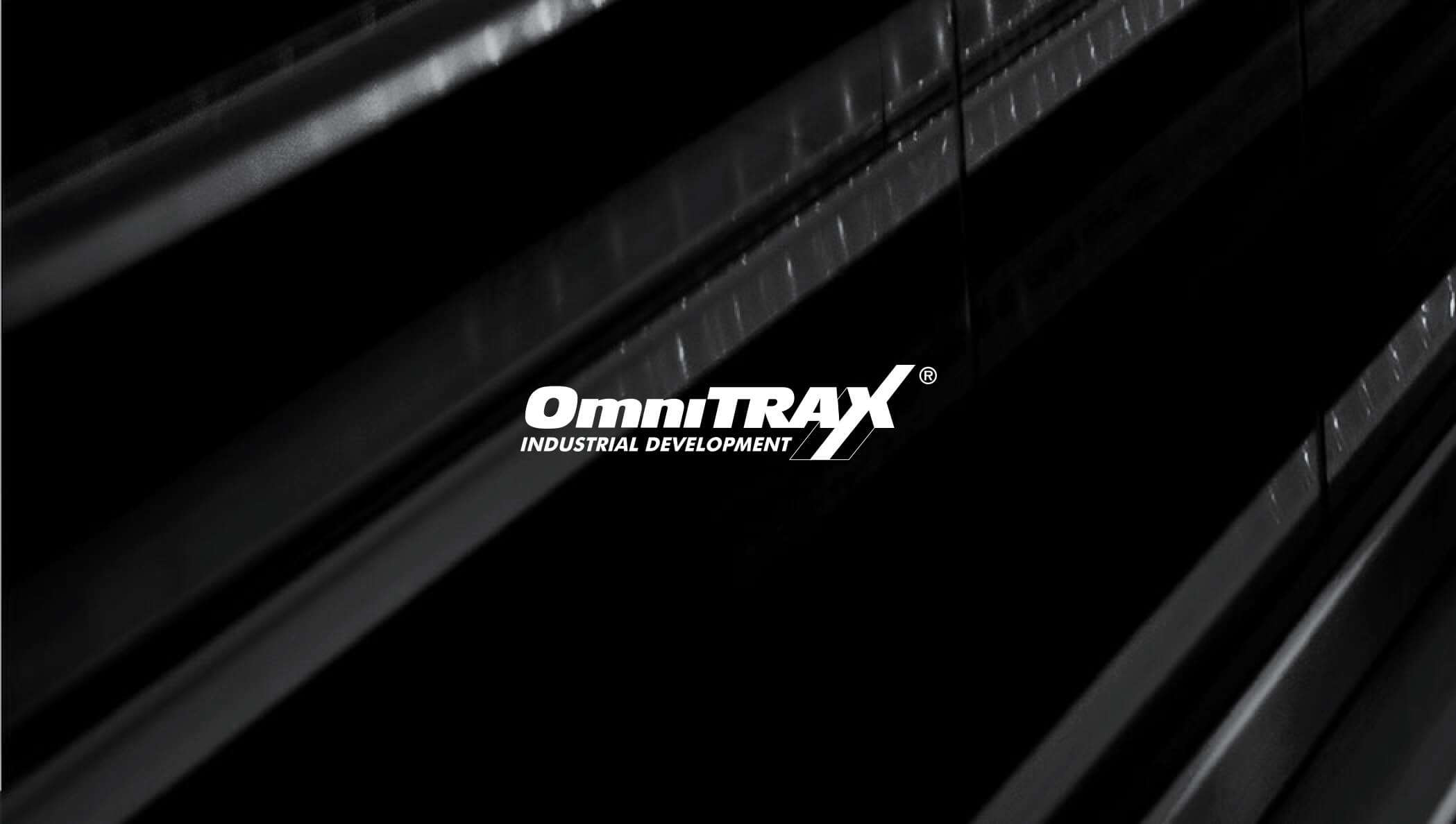 A white OmniTrax company logo sits in front of a dark gray abstraction of railroad tracks.