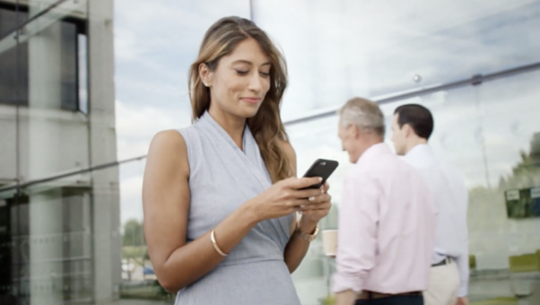 Woman smiling while looking at a device she is holding.