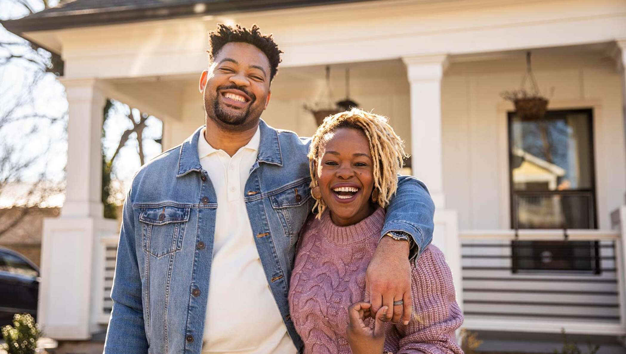 Image of two people outside their new home.