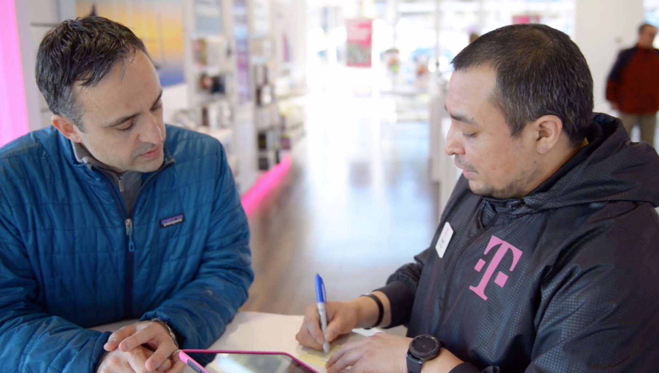 Two people in a T-Mobile office working through a phone contract.