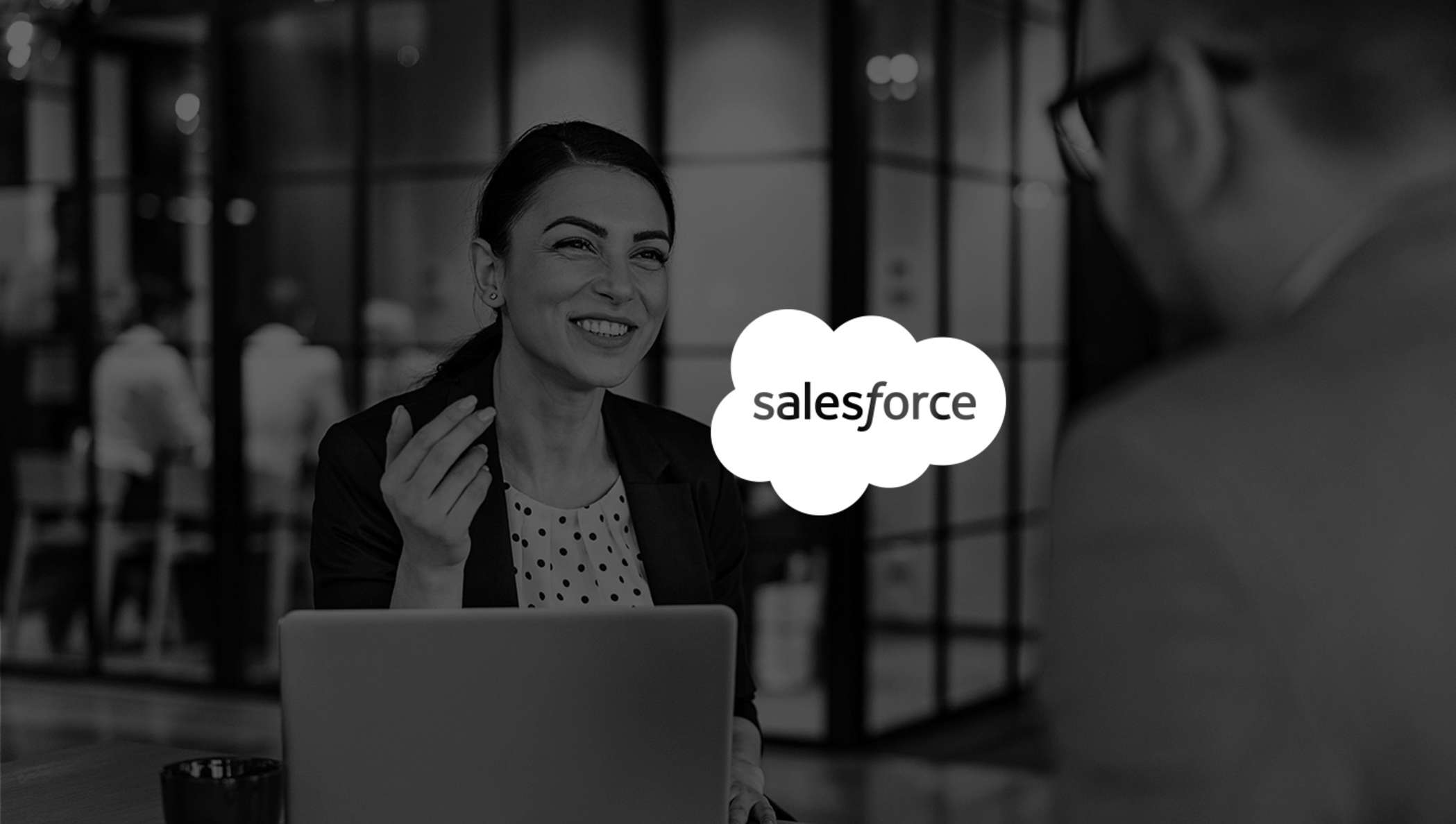 Image of woman smiling in meeting while using Salesforce with DocuSign.