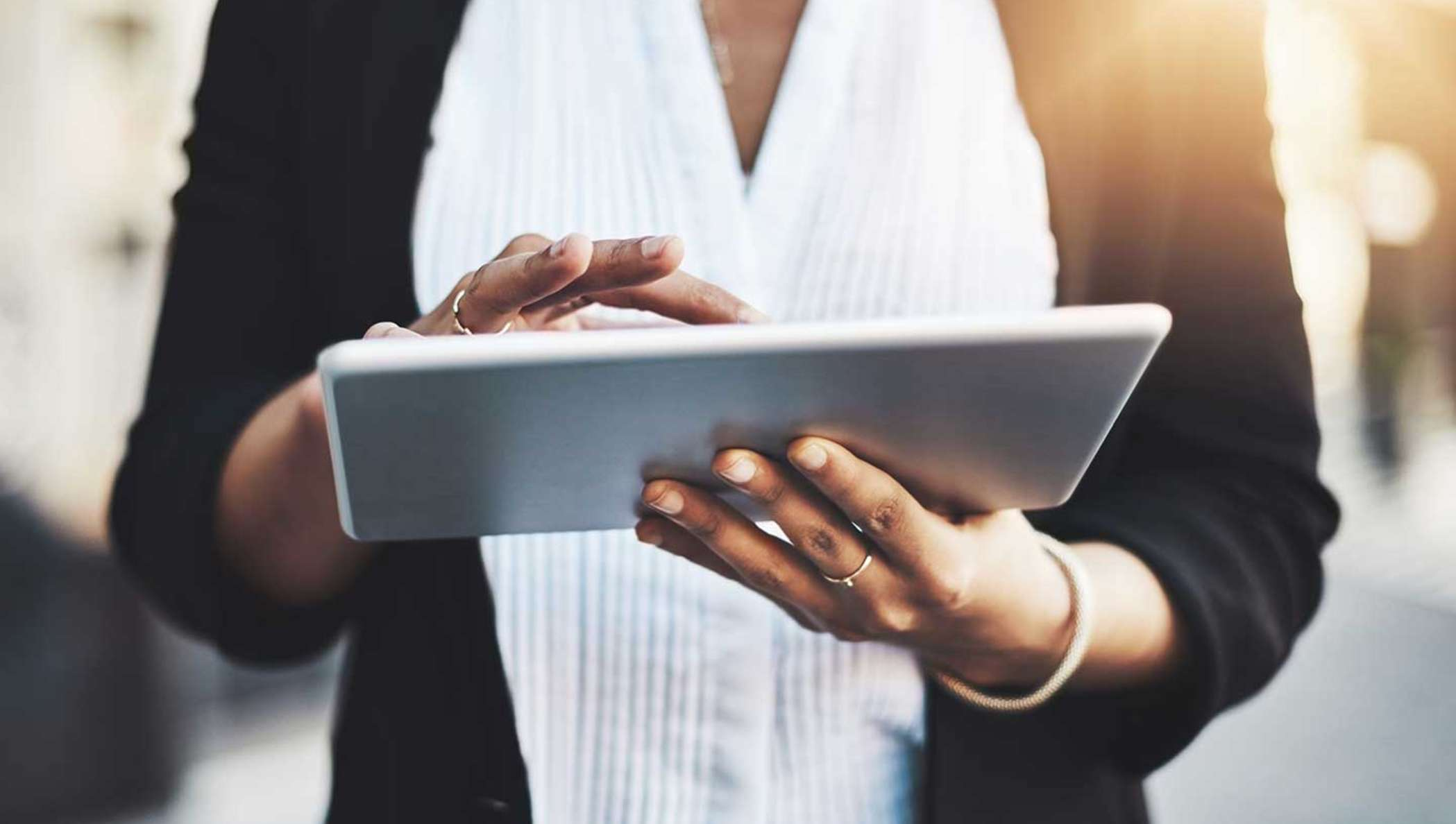 A businesswoman is checking her tablet for information on a document to sign