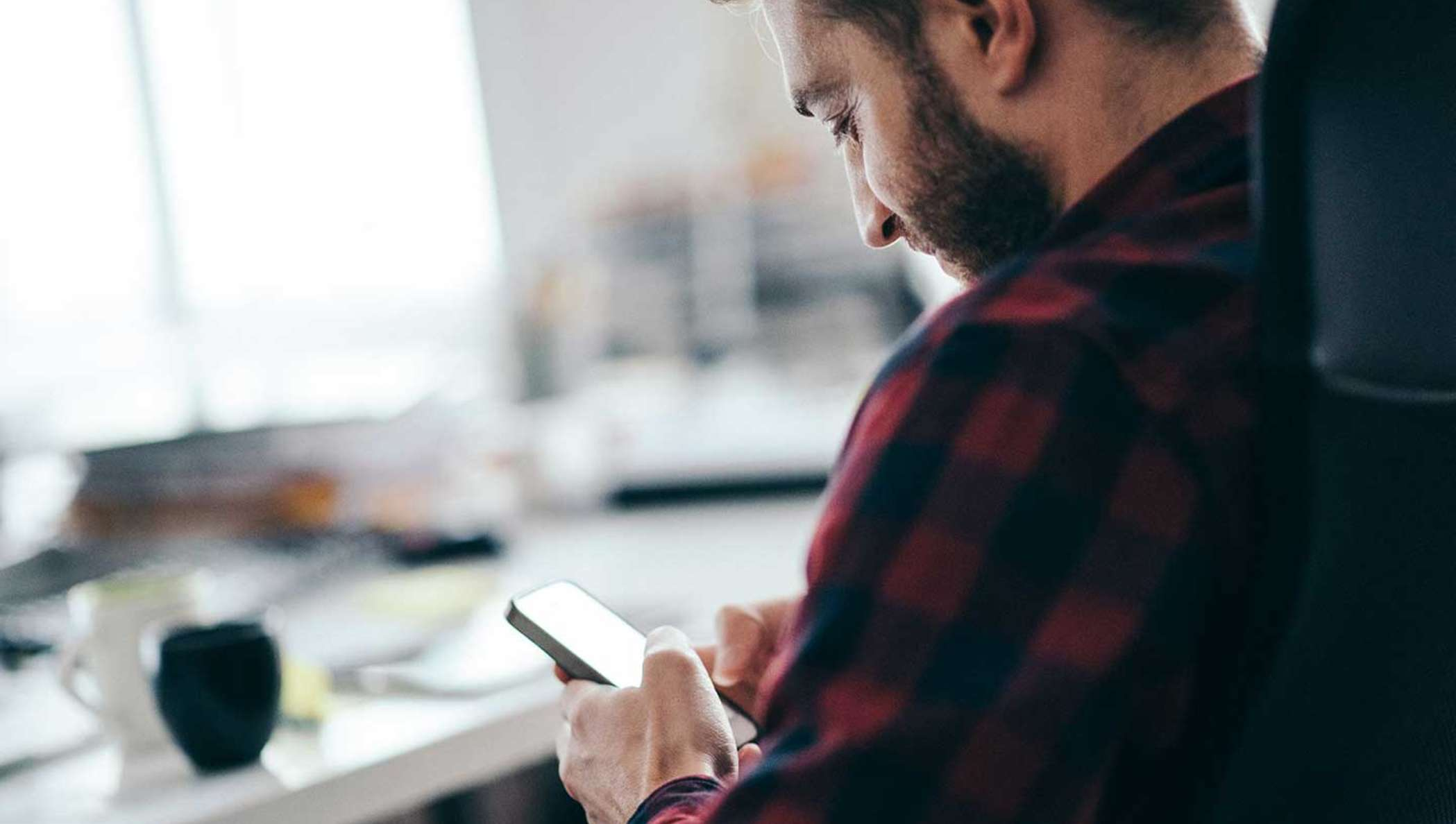 A bearded man in a flannel shirt checks the status of a document out for signature on his mobile phone