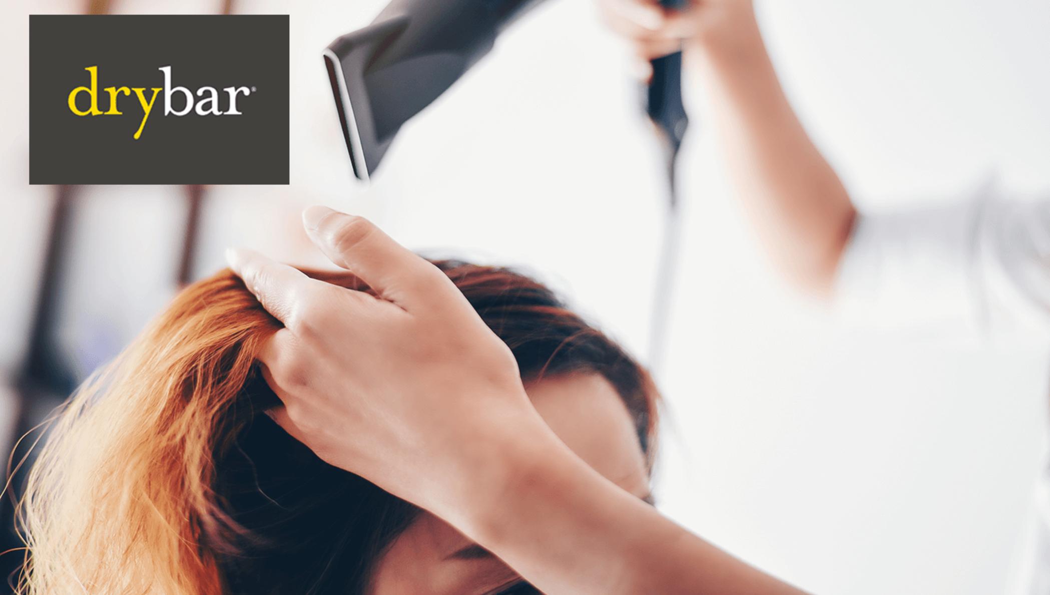 Drybar logo over a woman in a salon chair getting her hair dried.