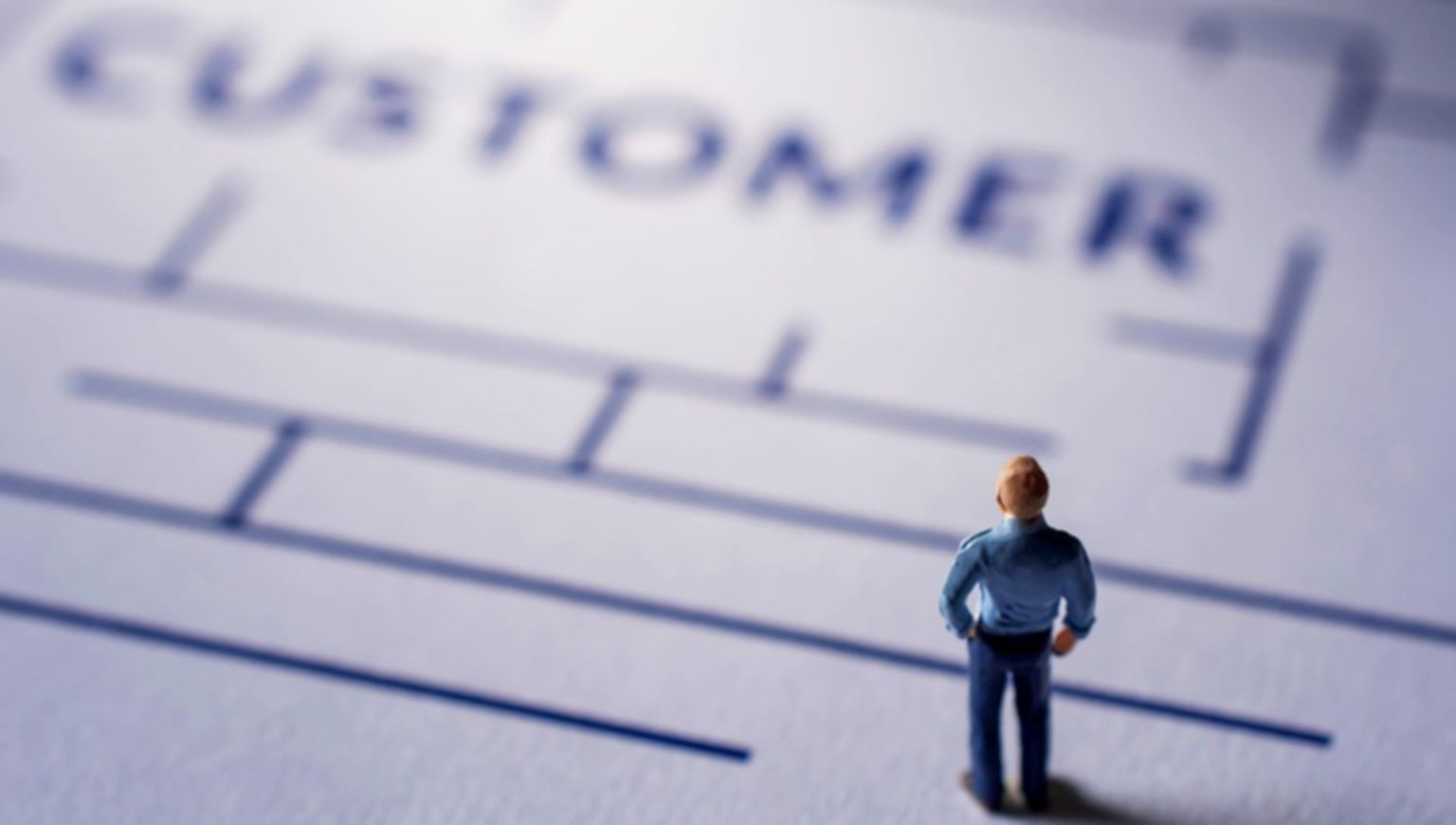 A miniture figurine man on a paper maze.